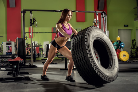 musculation: young fitness woman execute exercise with large tire casing, in gym, horizontal photo