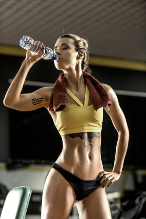 young fitness woman with bottle water in gym, vertical photo