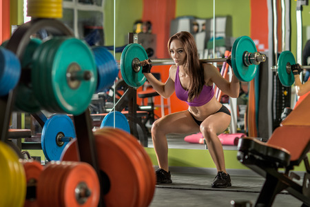 brawny: beautiful girl bodybuilder,  execute exercise squatting with  weight, in gym Stock Photo