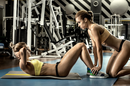 two young fitness woman, execute exercise on prelum abdominale in gym, horizontal photo Stock Photo