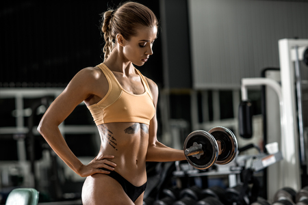 young fitness woman execute exercise with dumbbells in gym, horizontal photo