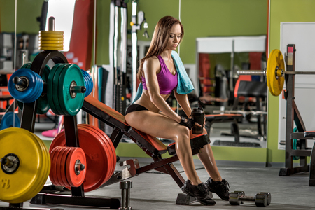 musculation: young fitness woman tired in gym hold shaker with sportive nutrition - protein of shaker , horizontal photo