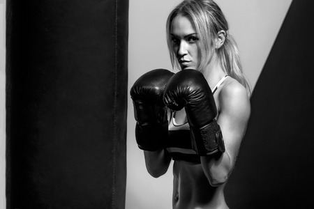 punching bag: young boxer woman in boxing gloves with punching bag , on black and yellow background, black-and-white horizontal photo