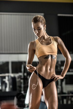 young fitness woman tired in gym and listen music with headset, vertical photo