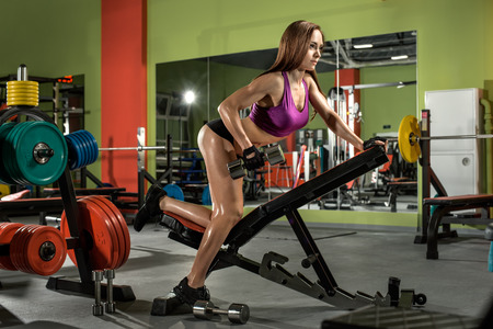 musculation: fitness girl  execute exercise with  dumbbells, on broadest muscle of back