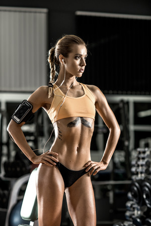 musculation: young fitness woman tired in gym and listen music with headset, vertical photo