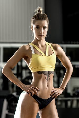 junge Frau Fitness ausführen Übung mit Hanteln im Fitness-Studio, vertikale Foto