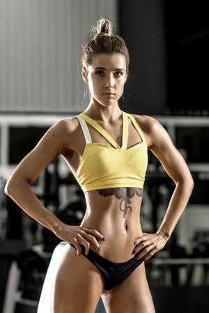 execute: young fitness woman execute exercise with dumbbells in gym, vertical photo