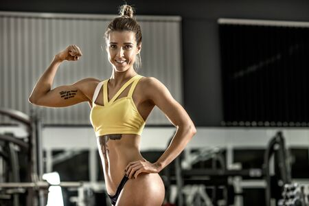 tough girl: young fitness woman in gym, smile, horizontal photo