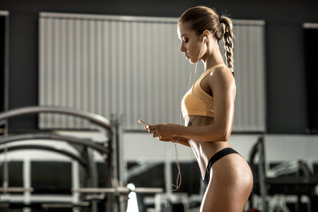 brawny: young fitness woman tired in gym and listen music with headset, side view, horizontal photo