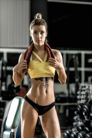 musculation: young fitness woman in gym, vertical photo