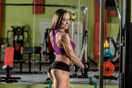 musculation: fitness girl, execute exercise with gym apparatus, horizontal photo Stock Photo