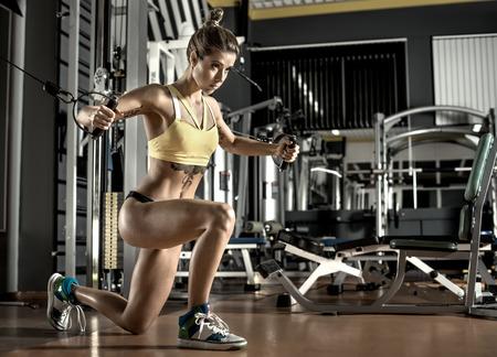 muskeltraining: junge Frau Fitness führen Sie Übung mit Übung-Maschine-Cable Crossover im Fitness-Studio, horizontale Foto