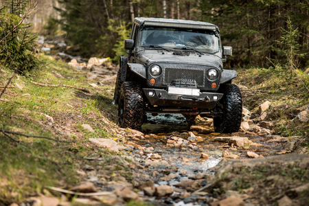 off-road extreme expedition on black jeep wrangler, in mountain terrain