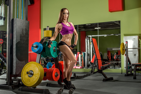 musculation: young fitness woman in gym, smile, horizontal photo