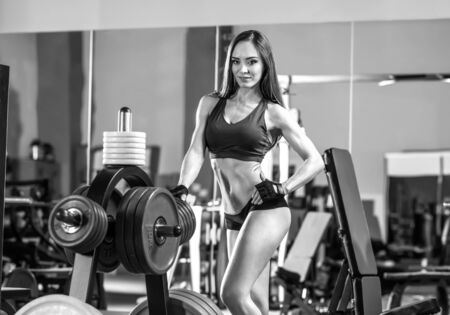 musculation: young fitness woman in gym, smile, horizontal black-and-white photo Stock Photo
