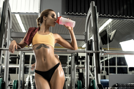 giovane donna di forma fisica in palestra stanco bevanda sportiva nutrizione, aminoacidi e BCAA di agitatore, foto orizzontale