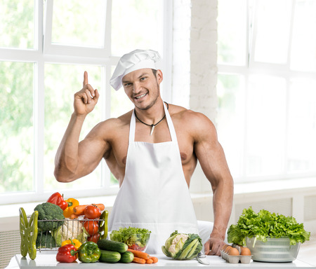 toque blanche: Man bodybuilder in white toque blanche and cook protective apron, concoction vegetables and fruit