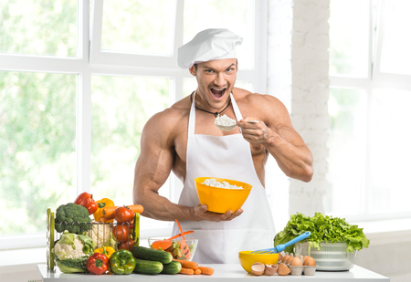 toque blanche: Man bodybuilder in white toque blanche and cook protective apron, eating cottage cheese , in white kitchen Stock Photo