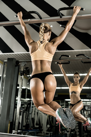 vertical bar: young fitness woman execute exercise on prelum abdominale, on horizontal bar in gym, vertical photo Stock Photo