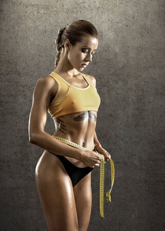 musculation: young fitness woman measure girth waist, with measuring tape, vertical photo