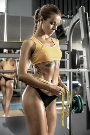 young fitness woman measure girth waist, with measuring tape, in gym, vertical photo