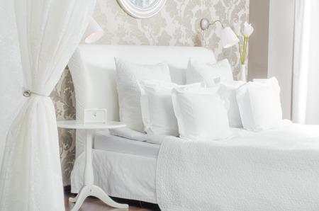 grand le lit double blanc dans la chambre de lumière, à l'hôtel ou à la maison