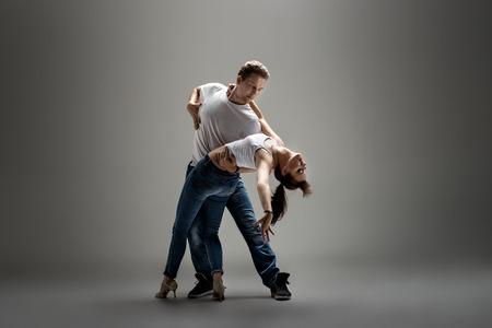 beauty couple dancing social danse ( kizomba or bachata or semba or taraxia) , on grey background Reklamní fotografie - 70135080