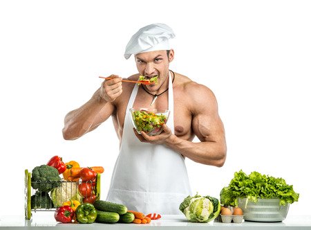 Man bodybuilder in white toque blanche and cook protective apron, gnaw salad , on whie background, isolated