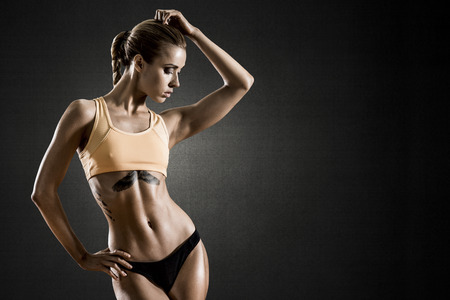 young fitness woman on dark, black background, horizontal photo