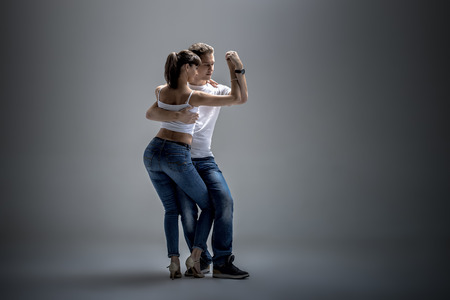 beauty couple dancing social danse ( kizomba or bachata or semba or taraxia) , on grey background