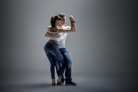 actitud: belleza pareja bailando danza sociales (kizomba o bachata o Semba o taraxia), sobre fondo gris