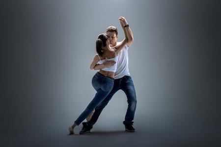 beauty couple dancing social danse ( kizomba or bachata or semba or taraxia) , on grey background Фото со стока - 70223271