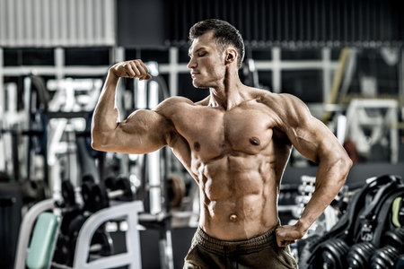 very power athletic guy ,  execute exercise with  dumbbells, on bkack background Reklamní fotografie