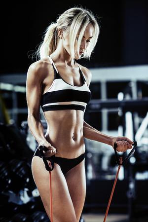 muskeltraining: junge Frau Fitness führen Sie Übung mit Expander im Fitness-Studio, vertikale Foto
