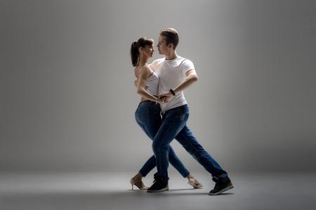 아름다움 커플 회색 배경에 사회적 danse (kizomba 또는 bachata 또는 semba 또는 taraxia) 춤