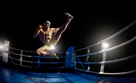 Thai boxer on boxing ring, jump and kicking, black bacground, horizontal photo Stock Photo