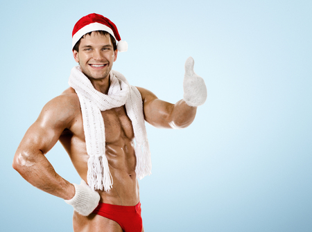 fitness sexy Santa Claus in  white scarf, smile, on blue background photo