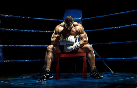 timeout: boxer on boxing ring, tired time-out,  black bacground, horizontal photo