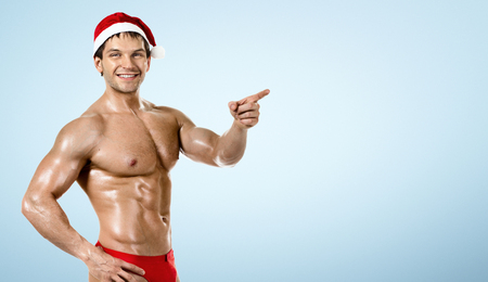 fitness sexy Santa Claus , show index finger and smile, on blue background photo