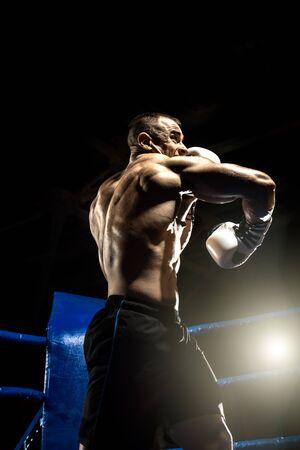 punching boxer on boxing ring, black bacground, vertical photo