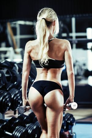 musculation: young fitness woman with dumbbells in gym, body back, vertical photo