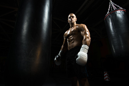boxer in gym with punching bag, black bacground, horizontal photo