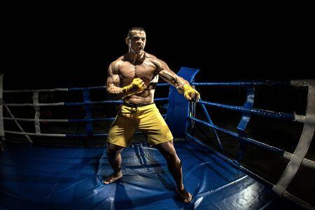 Thai boxer on boxing ring, black bacground, horizontal photo