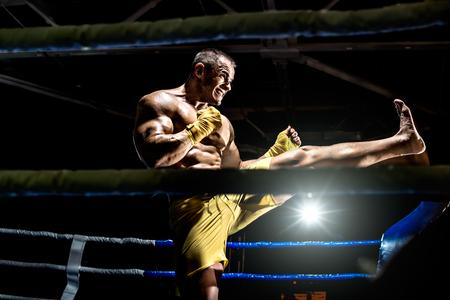 Thai boxer on boxing ring, kicking, black bacground, horizontal photo