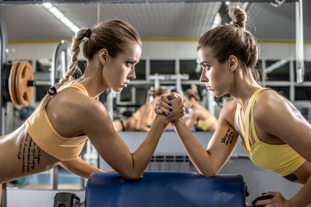 two young fitness woman, arm wrestling in gym, horizontal photo