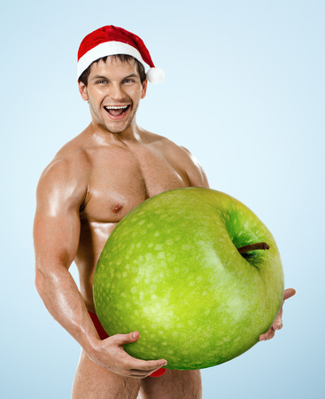 fitness sexy Santa Claus on blue background, hold great green apple and laughing photo