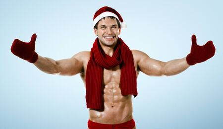 fitness sexy Santa Claus in red muffler,  smile, on blue background photo
