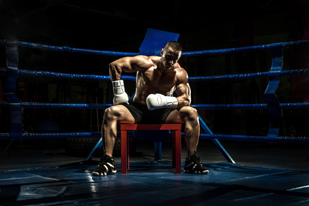 brawny: boxer on boxing ring, tired time-out,  black bacground, horizontal photo