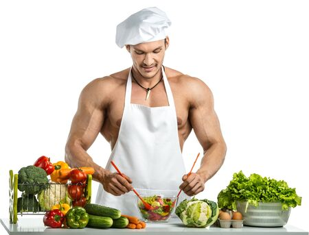 Man bodybuilder in white toque blanche and cook protective apron, concoction vegetables salad; lettuce , on whie background, isolated